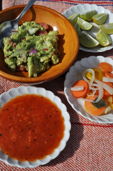 Typical healthy condiments: guacamole, salsa, rajas (pickled carrots, onion, and jalapeño peppers) and limes