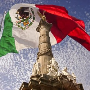 Mexican flag flying behind the Angel of Independence monument in Mexico City.